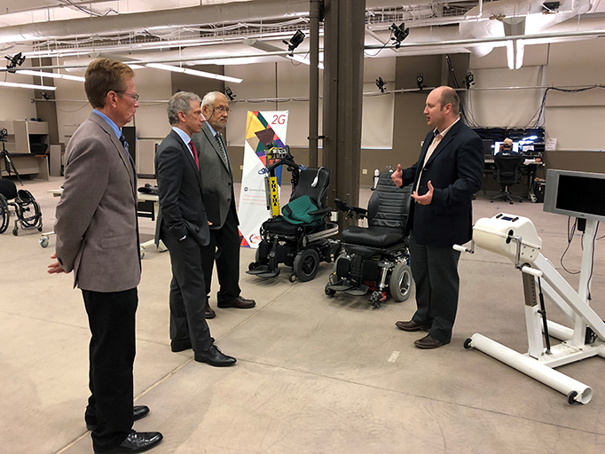 John Kaplan, Andrei Iancu, and Al Langer stand in a room with Dr. Garrett Grindle surrounded by wheelchairs and other accessible technology.