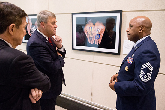 Lt.Gen. David Halverson speaks to a USPTO employee in front of the veteran keepsake gallery.