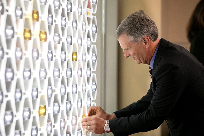 Stan Honey inserts his name plaque into a hexagonal icon at the NIHF museum.