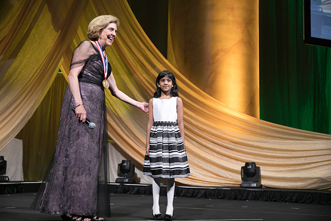 A woman stands on stage smiling with a young girl.
