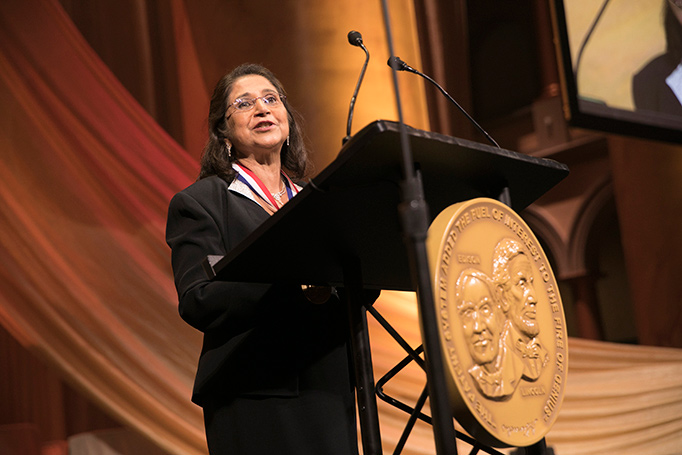 2018 NIHF inductee Sumita Mitra speaks behind a podium at the 2018 induction ceremony.