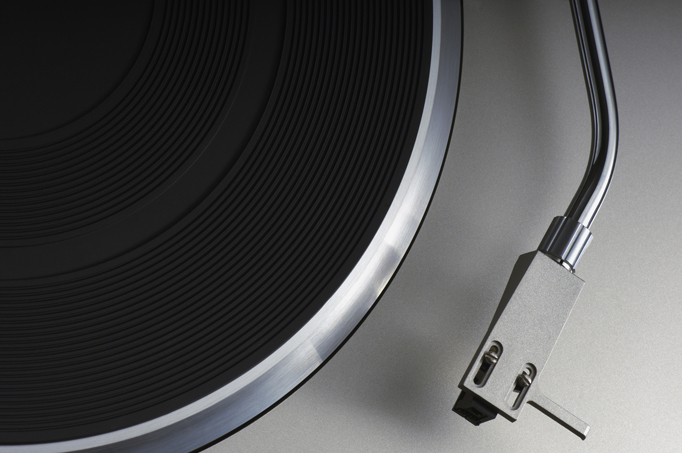 Top down photo of a record player on a grey background.