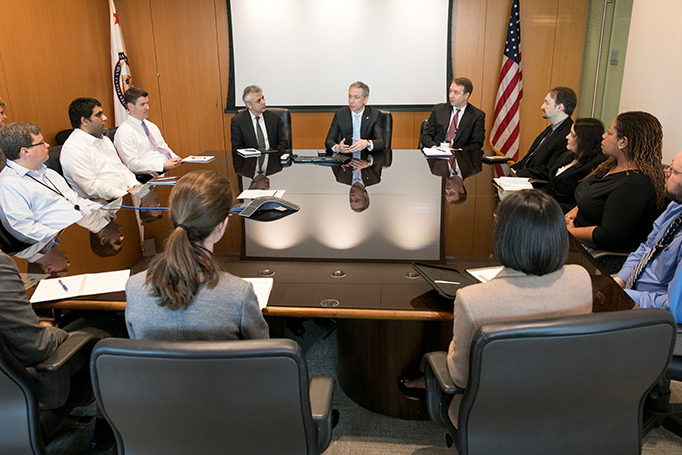 Director Iancu sits at the center of a large conference table , speaking with employees.