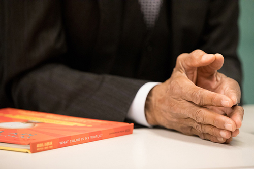 "A book titled ""What Color is my World?: The Lost History of African-American Inventors"" authored by Kareem Abdul-Jabbar sits on a table next to the author's hands."