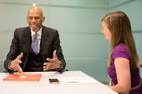 Kareem Abdul-Jabbar sits across from interviewer smiling and gesturing with his hands.