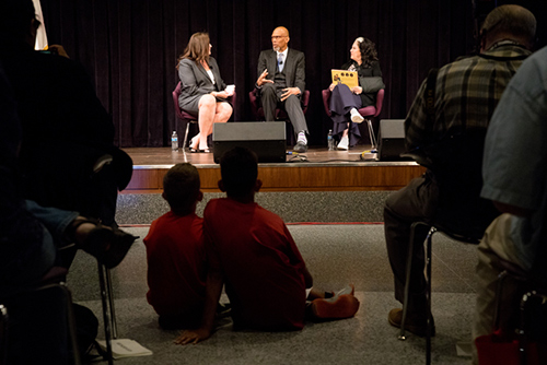 Two children look on as three people sit on a stage for a discussion.