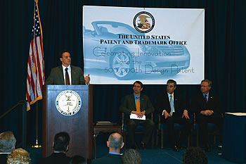 Photo showing (Left to right) Under Secretary Jon Dudas, Deputy Under Secretary Steve Pinkos, Secretary Gutierrez, and Vice President of Design for Daimler/Chrysler Trevor Creed joining in celebrating the 500,000th U.S. design patent.