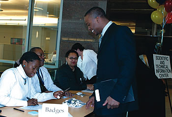 Photo showing employees from the Office of Human Resources greeting and registering interested candidates during a U S P T O job fair.