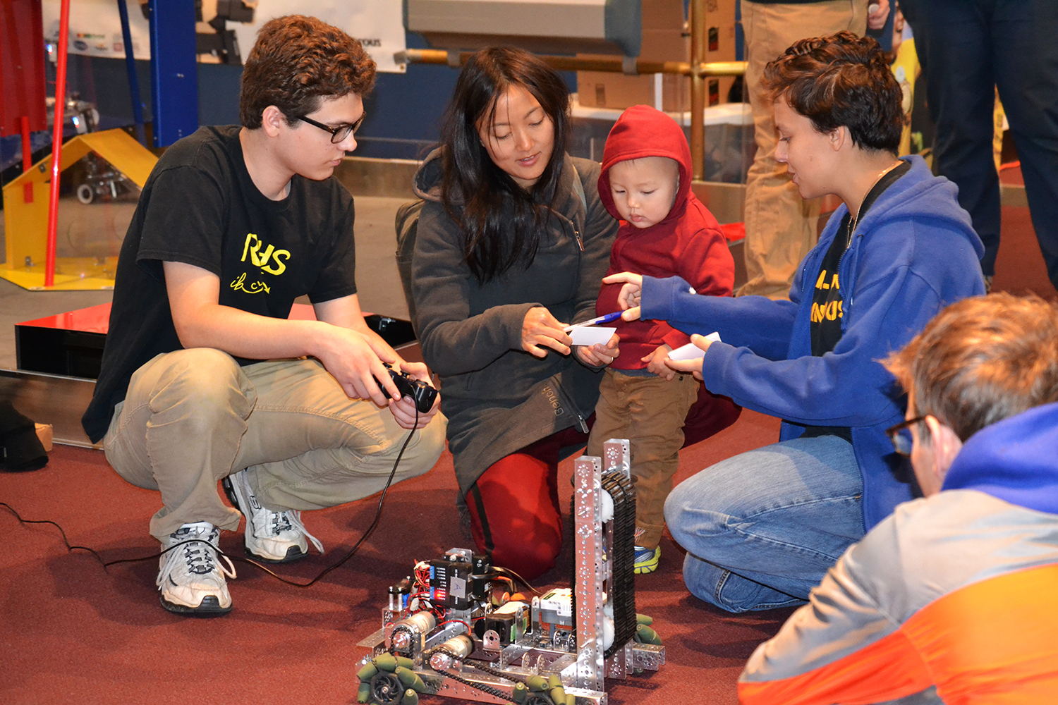 A student demonstrates a FIRST robot to onlookers