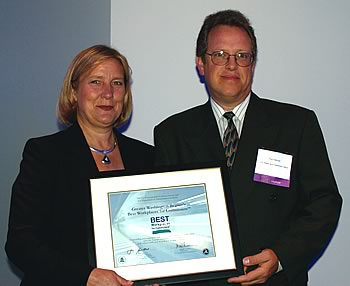Photo showing Suzanne Rudzinski, Director, of the EPA's Transportation and Regional Programs presenting to the USPTO's Tom Hellmer an award recognizing the USPTO as one of the best workplaces for commuters.