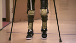 Photo showing a pair of legs aided by crutches and an exoskeleton