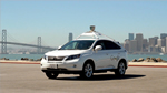Photo of a white driverless car with a cityscape in the background