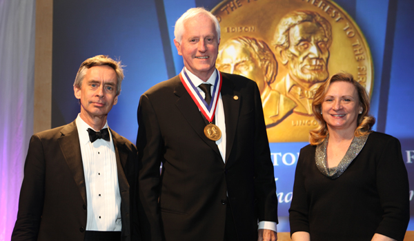 Three people, one wearing a medallion, pose in front of a backdrop of a coin with the images of Lincoln and Edison engraved on it