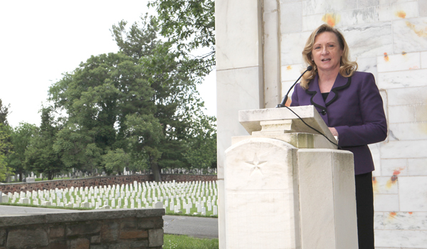 Official speaks from stone lectern with marble wall behind her and cemetery gravestones in background