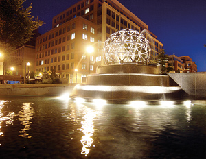 Photo showing a sculpture in a water fountain near the U.S. Patent and Trademark Office buildings at night.