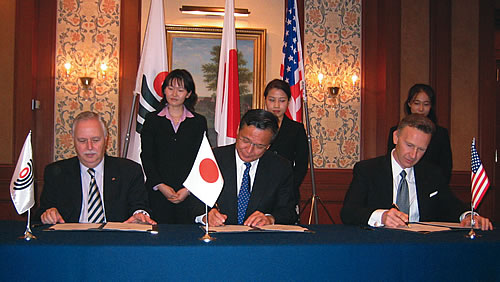 Photo showing Former Under Secretary Rogan signing agreements at the 21st Annual Patent Trilateral meeting in Tokyo. Joining the Under Secretary at the signing ceremony are Yasuo Imai, (center) Commissioner of Japan's Patent Office and Ingo Kober (left), President of the European Patent Office.