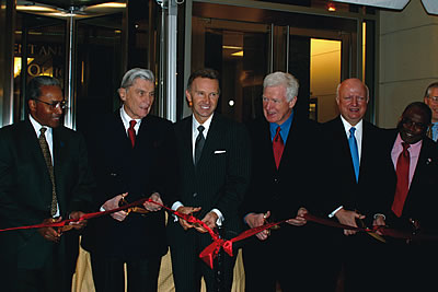 Photo showing ribbon cutting ceremony at the new USPTO Headquarters in Alexandria. Preparing to cut the ribbon are: Stephen A. Perry, Administrator General Services Administration, Sen. John Warner, James E. Rogan, Former Under Secretary of the USPTO, Rep. James Moran, Samuel Bodman, Deputy Secretary of Commerce, and Mayor William D. Euille.