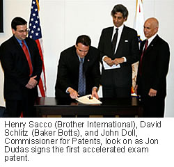 Henry Sacco (Brother International), David Schlitz (Baker Botts), and John Doll, Commissioner for Patents, look on as Jon Dudas signs the first accelerated exam patent.