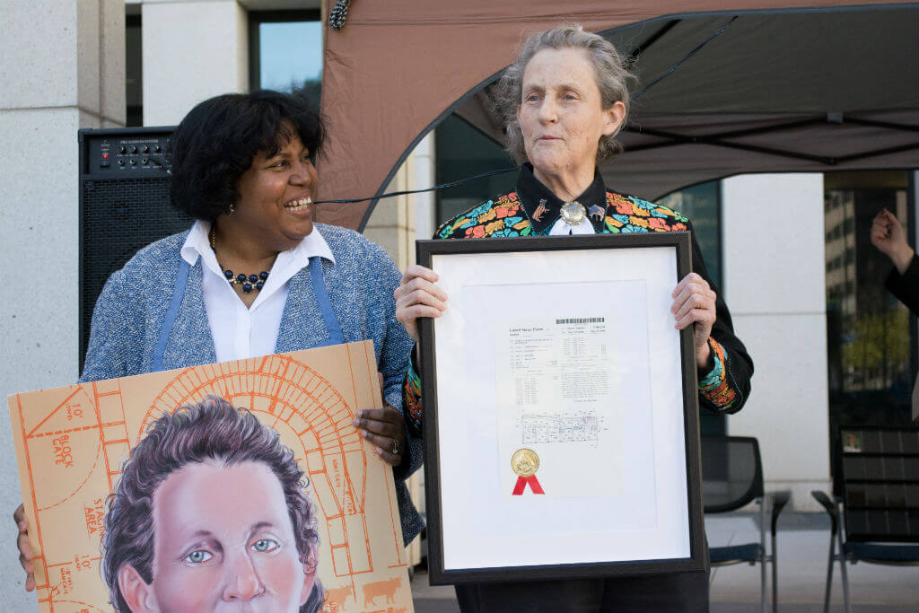 Image: Grandin holds up patent no. 5,906,540 for her invention of an animal stunning system, while Joyce Ward from USPTO's Office of Education and Outreach (left) presents Grandin with an oversized copy of an inventor trading card depicting Temple and her livestock handling designs.