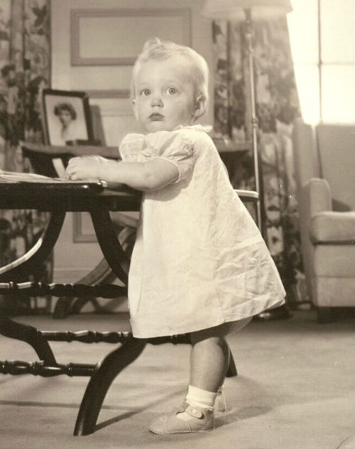 Image: Black and white photo of toddler Temple Grandin in white dress and fancy shoes.