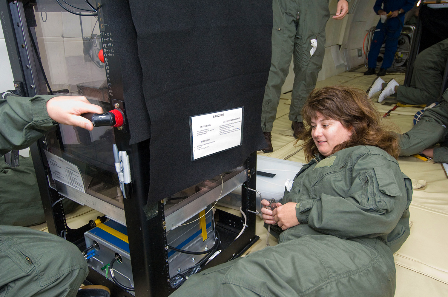 Jackie Quinn examines a piece of equipment on the ground with four team members working in the background