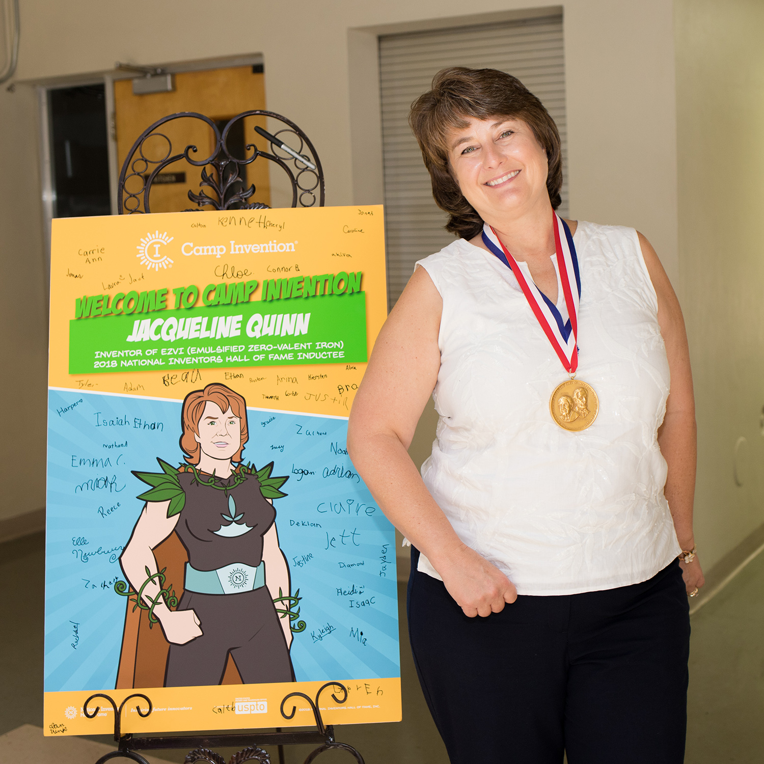 Jackie Quinn poses with her Camp Invention poster, autographed by campers