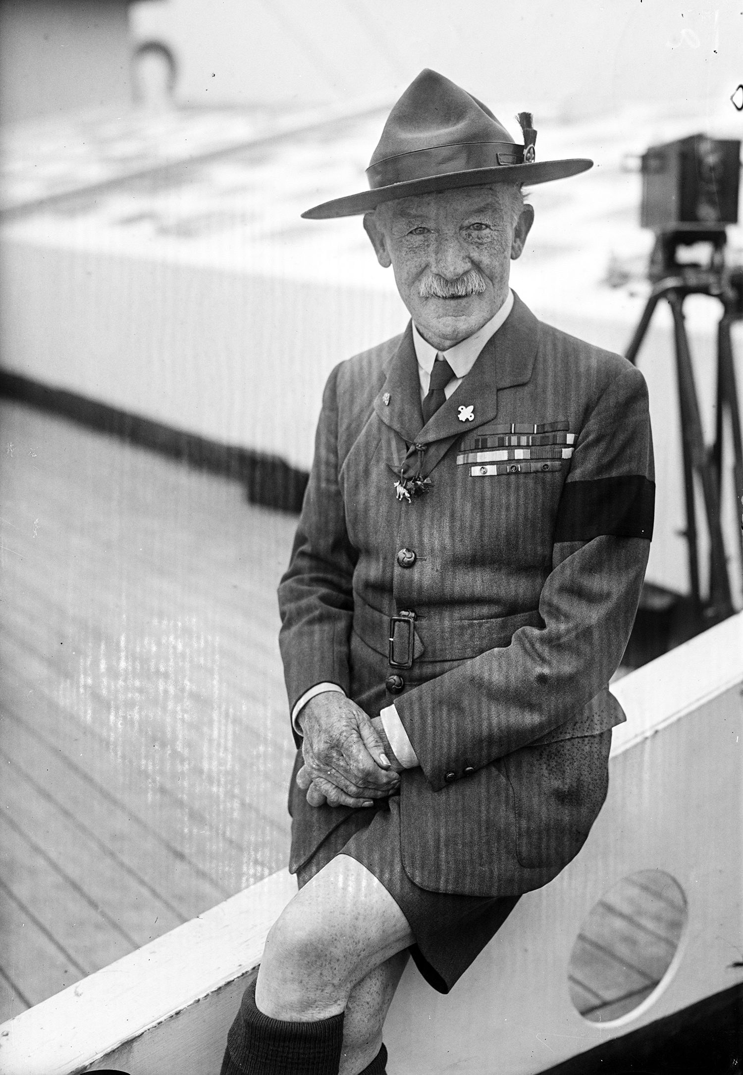 Robert Baden-Powell, smiling, in uniform and wearing military decorations on his chest and a wide-brimmed hat, photographed on the roof of a building.