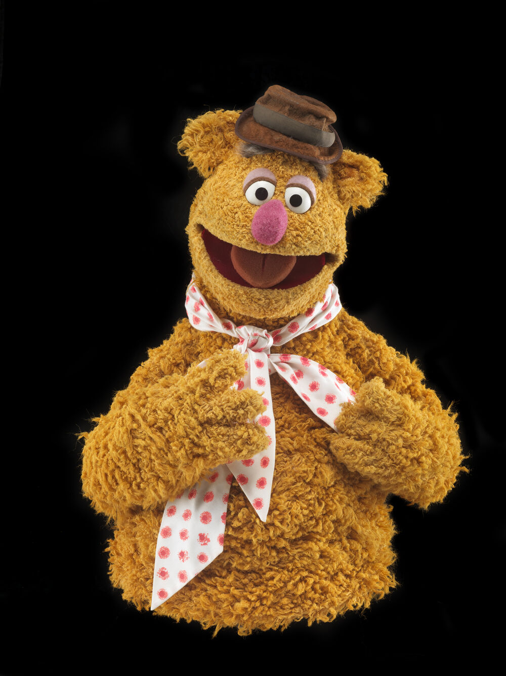 The Fozzie Bear puppet, created by Jim Henson, wearing a hat and polka dot bow tie.