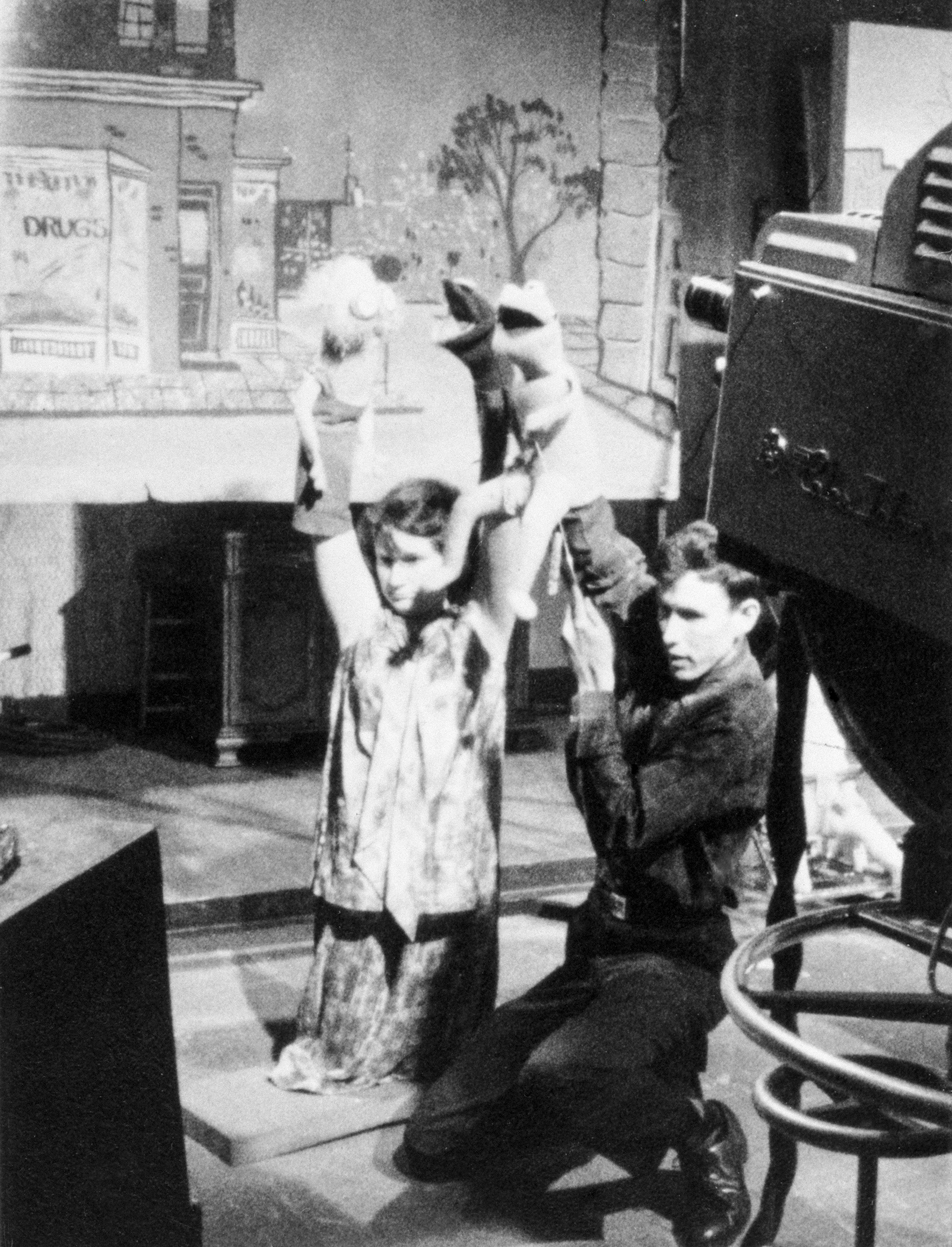 """Jim and Jane Henson on their knees performing with their puppets in front of a television camera and television monitor on the set of """"Sam and Friends."""""""