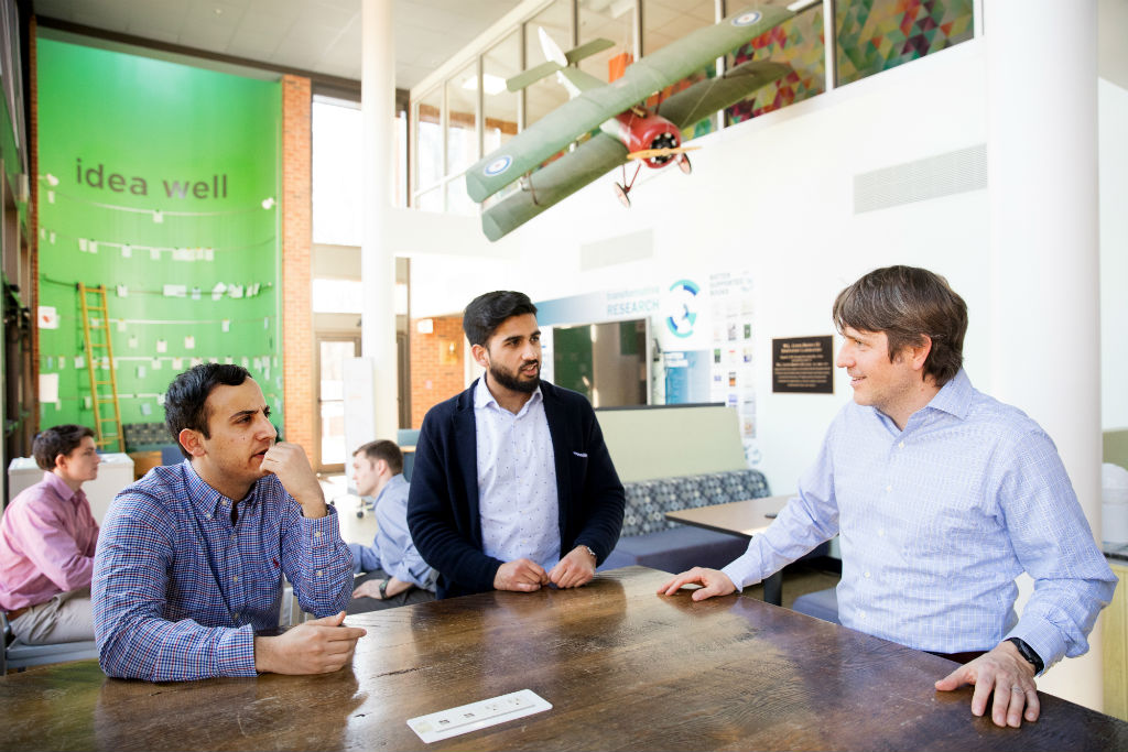 From left, Payam Pourtaheri and Ameer Shakeel visit with Jason Brewster, the incubator program director at University of Virginia i.Lab. As a startup at the incubator, AgroSpheres received initial funding, access to mentors, and a workspace.
