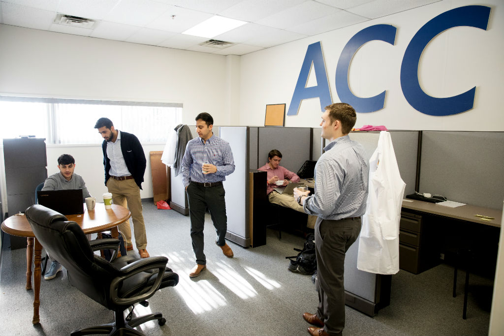 Sepehr Zomorodi, Ameer Shakeel, Payam Pourtaheri, Joseph T. Frank, and Zachery Davis begin their day discussing emails and work over coffee. On the wall above are the initials for the Atlantic Coast NCAA athletic conference, to which their alma mater, UVA, belongs. The team members are big supporters of UVA athletics.