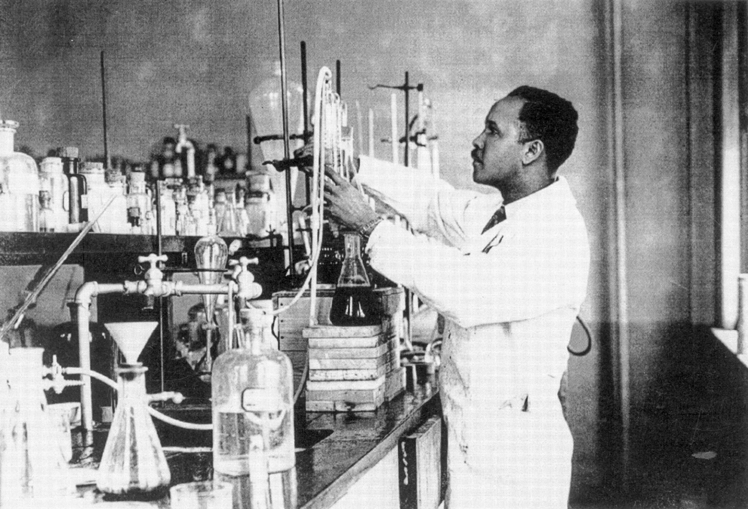 A man in a white coat works with equipment in a laboratory.