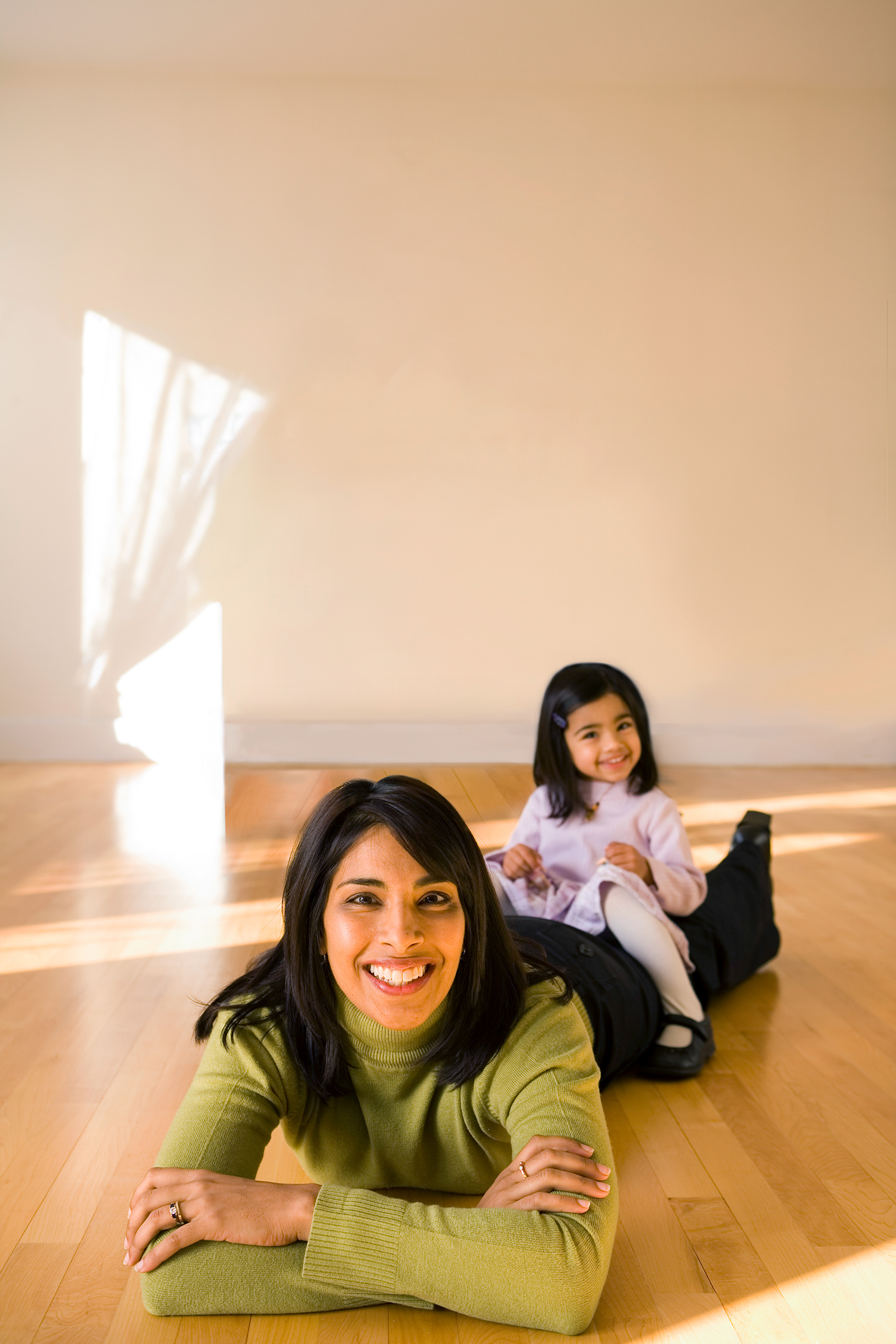 Sangeeta Bhatia lies on a wooden floor and is propped up on her elbows. Her daughter sits on her legs.