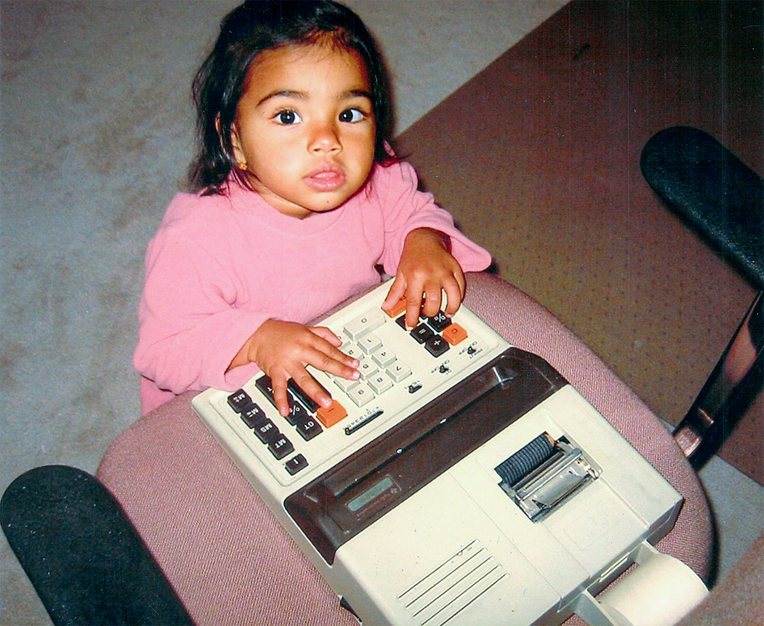 Sangeeta Bhatia, age 2, places both hands on a large calculator.