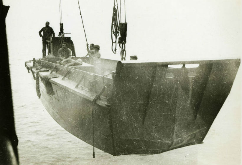 Image: Soldiers standing in a Higgins boat, which is being lowered into the water on ropes from a larger navy ship.