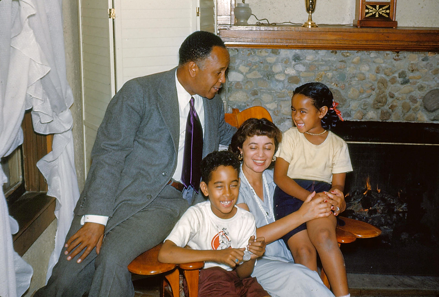 Percy Julian sits on the arm of a chair in which his wife and son are seated. His daughter sits on the opposite arm.
