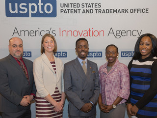 Five members of the USPTO and MBDA pose in front of a media backdrop.