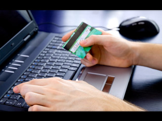 Man holding credit card above laptop keyboard