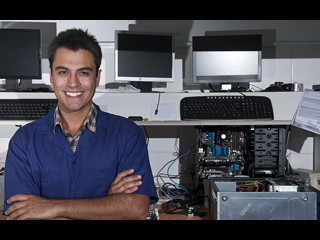 Man standing proudly infront of computers