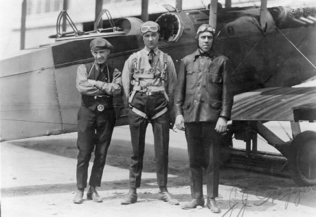 Three men stand in front of a biplane. The man in the middle wears a parachute.