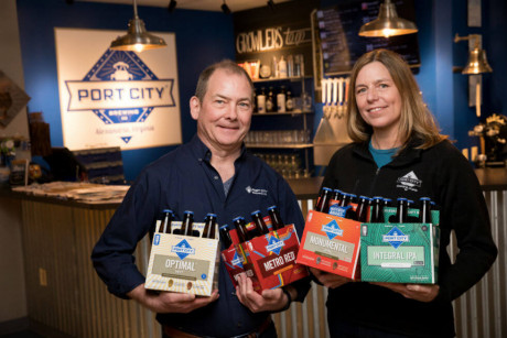 Image: Port City® Brewing Company founders Bill and Karen Butcher in the brewery's taproom hold six packs of some of their registered trademark beers, including, from left, Optimal® Wit, Metro Red®, Monumental® IPA, and Integral® IPA.