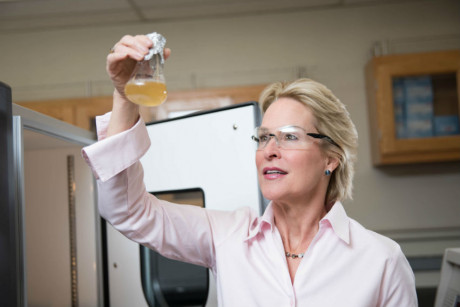 Image: Chemist Frances Arnold holds a beaker with yellow liquid up to the light.