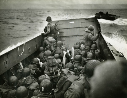 Image: Helmeted U.S. soldiers look out over the prow of a Higgens boat as it navigates crashing waves towards the beaches of Normandy on D-Day.