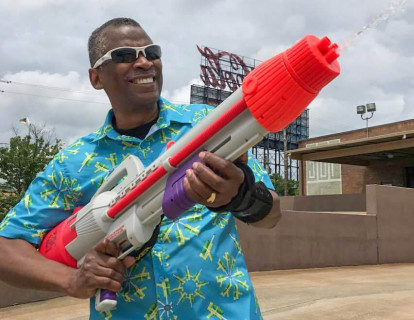 Image: Johnson plays around with a Super Soaker® while wearing a shirt patterned with images of his famous creation.
