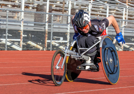 Rory Cooper  in leaned back in a racing chair on a red track, leaned down to become aerodynamic, pushing himself to win