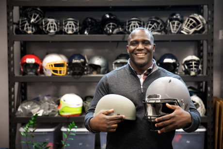 Shawn Springs holds two helmets and poses in front of a wall of helmets.