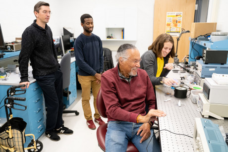 Jim West seated in his lab and surrounded by three students