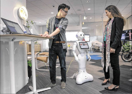 Susann Keohane and co-worker at the IBM aging in place environment/lab with the friendly looking Multi-Purpose Eldercare Robot Assistant (IBM MERA), a first of a kind Watson-enabled application designed to aid the elderly and assist caregivers with real-time information about their health.