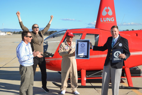Martine Rothblatt(excitedly jumping)  and the team from Tier one engineering proudly celebrating in front red Electric helicopter that, with the word lung written on it, huge smile, that just set  Guinesss World Record  being awarded plaque