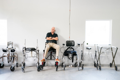 garrett brown sitting in middle of evolution of six chairs in white studio